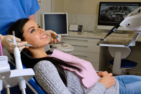 Beauty brunette having teeth examined at dentists.
