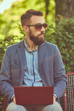 Close-up portrait of a writer with a full beard and stylish haircut, working with a laptop computer while sitting on a bench in a city park.