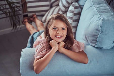 Portrait of a happy little girl with long brown hair and charming smile, looking at a camera, lying on a sofa at home