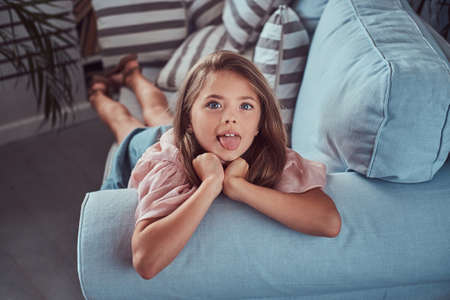 Portrait of a happy little girl with long brown hair and piercing glance, shows tongue on the camera, lying on a sofa at home Stock Photo