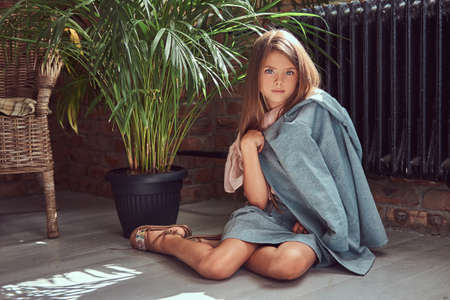 Cute little girl with long brown hair wearing a stylish dress, sitting on a wooden floor in a room with a loft interior
