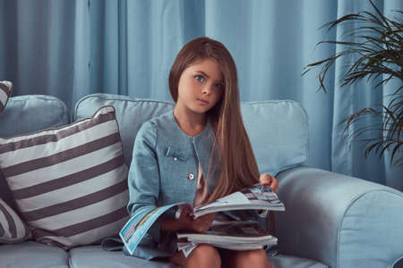 Cute stylish little girl with long brown hair, sitting on a sofa, holds fashion journals