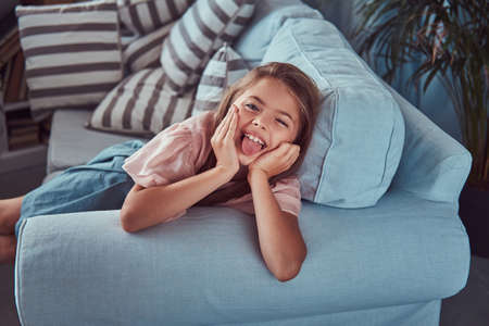 Portrait of a happy little girl with long brown hair and piercing glance, shows tongue on the camera, lying on a sofa at home Reklamní fotografie