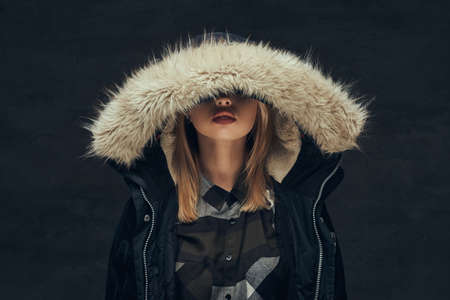 Portrait of a sexy blonde girl in a winter jacket and fleece shirt, standing in a studio.