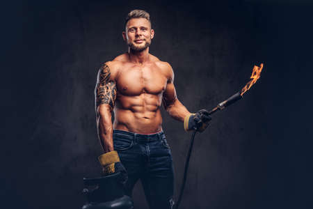 Brutal tattoed male welder with a stylish haircut and beard, with muscular body, dressed in only jeans, holds propane tank and a burning burner, standing in a studio, looking at a camera.