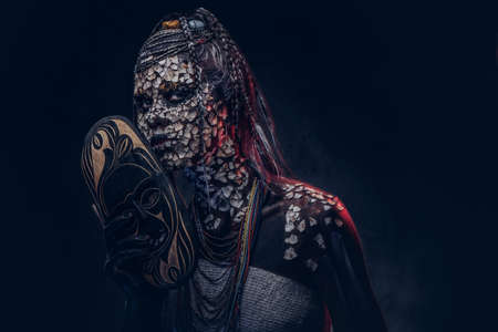 Make-up concept. Portrait of a scary African shaman female with a petrified cracked skin and dreadlocks, holds a traditional mask on a dark background. Make-up concept.