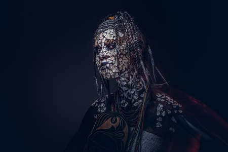 Close-up portrait of a witch from the indigenous African tribe, wearing traditional costume. Make-up concept.