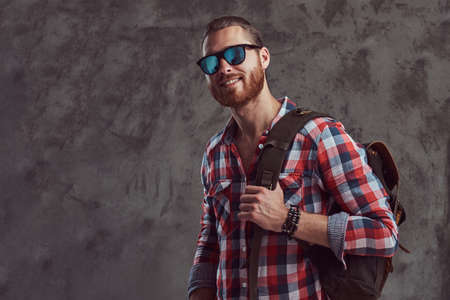 Handsome stylish redhead traveler in a flannel shirt and sunglasses with a backpack, posing in a studio on a gray background.