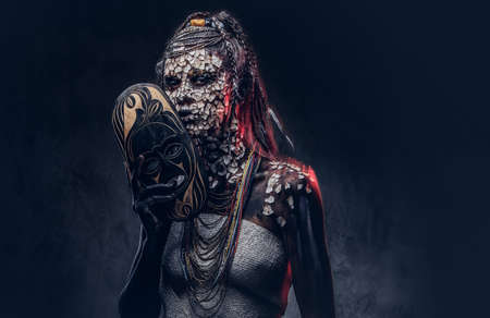 Make-up concept. Portrait of a scary African shaman female with a petrified cracked skin and dreadlocks, holds a traditional mask on a dark background. Make-up concept. Stock Photo - 100516875
