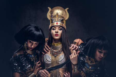 Portrait of haughty Egyptian queen in an ancient pharaoh costume with two concubines. Stock Photo
