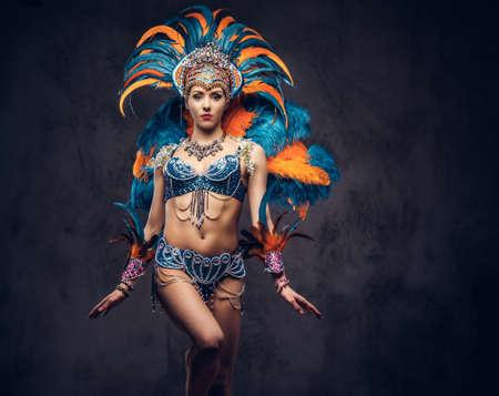 Studioporträt einer Frau in einem bunten prächtigen Karnevalsfederanzug. Auf einem dunklen Hintergrund isoliert.