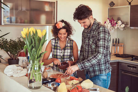 Beautiful young couple cooking in the kitchen at home.