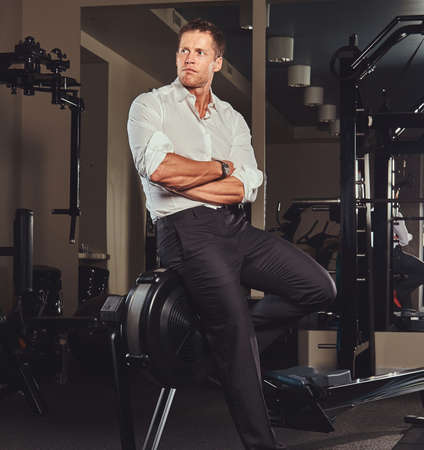 Handsome confident businessman in formal clothes came to the gym for training after a hard days work. Imagens