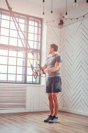 Muscular fitness male doing exercise with suspensions straps. Functional workout at home with suspensions straps loops.
