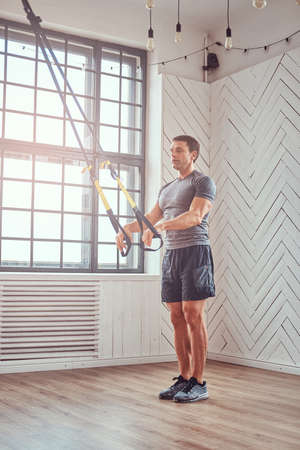 Muscular fitness male doing exercise with suspensions straps.