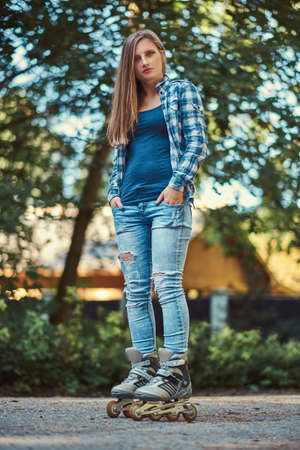Portrait of a beautiful girl with long hair wearing fleece shirt and jeans in rollers, standing in the park in summer day.