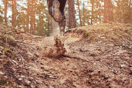 Athlete running along the forest trail. An active way of life, rear view. Banco de Imagens