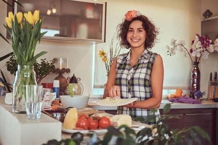 Charming curly Hispanic girl cooking in her kitchen. Standard-Bild