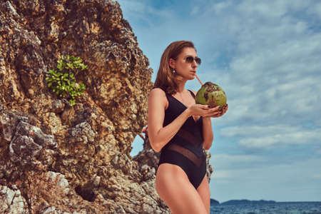 Beautiful woman in a swimsuit, holds coconut with a tube, standing on a beach near big reef stones, enjoys a vacation on a beautiful island.