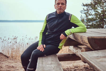 Jogger sits on a wooden bench in the woods, resting after a long run. Active way of life. Stock fotó - 101079272