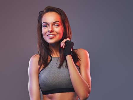 Smiling fitness brunette woman in a gray sportswear posing in a studio.