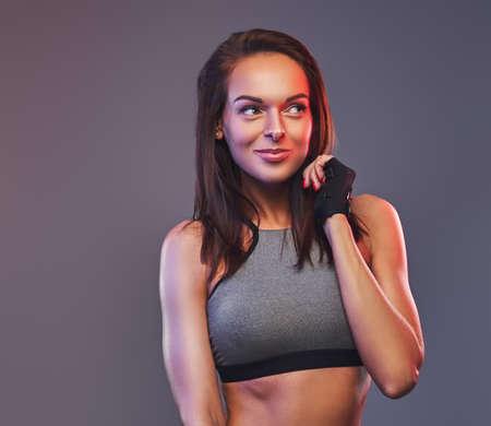 Slim fitness brunette woman in a gray sportswear posing in a studio.