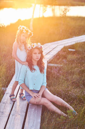 Two beautiful sisters standing against the background of a beautiful landscape, walk on the field near a pond at sunset.