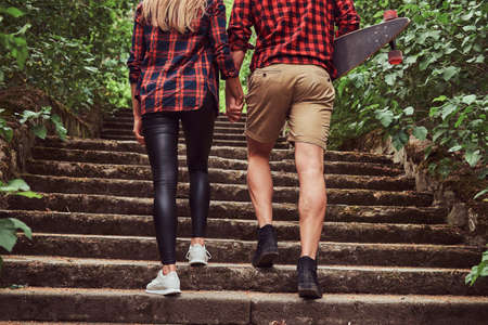 Young hipster couple, walk in a park, holding hands, climbing up the stairs.