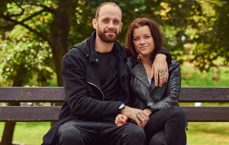 Attractive modern couple sitting on a bench in a park.