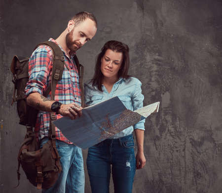 Studio portrait of male and female tourists with backpack and map, standing in a studio.