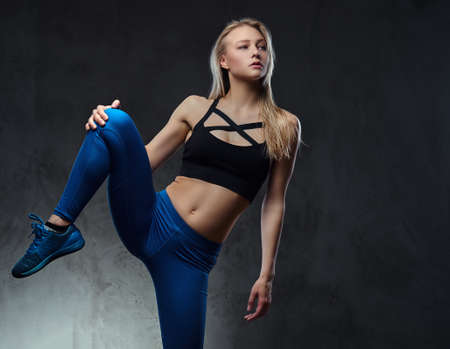 Young blonde graceful ballerina stretching and posing in a studio. Isolated on a dark background.