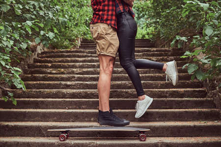 Cropped image of young hipster couple, cuddling while standing on steps in a park.