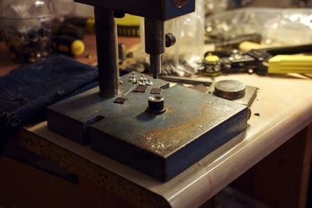 Picture of a tailors desktop with tools and rivet press.