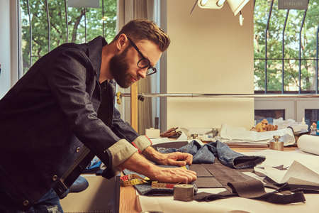 Handsome bearded tailor makes measurements of jeans cloth samples at sewing workshop. Stock Photo