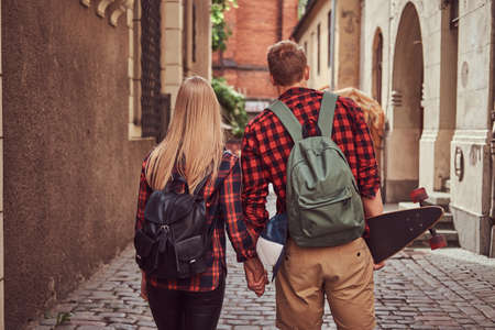 Back view of a young hipster couple, handsome skater and his girlfriend, holding hands, walking around a old narrow streets of Europe.