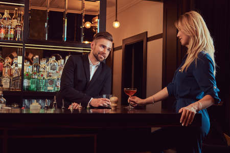 Stylish couple is spending the evening in a romantic setting, drinking wine at the bar counter. Banque d'images