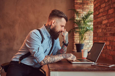 Handsome tattooed hipster in a shirt and suspenders sitting at the desk, working on a laptop, in an office with loft interior.