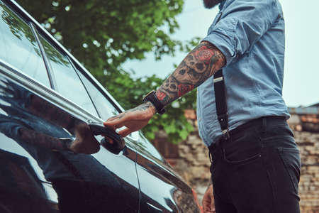 Cropped image of an old-fashioned tattooed man in a shirt with suspenders, who is going to get into a car.