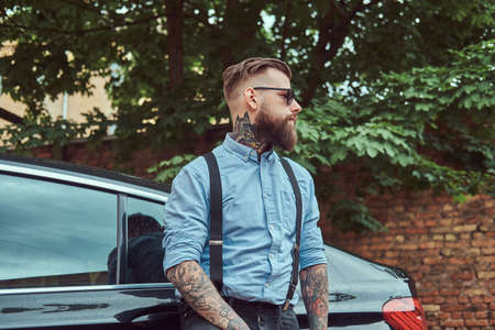 Old-fashioned tattooed hipster guy in a shirt with suspenders, standing near black car outdoors.