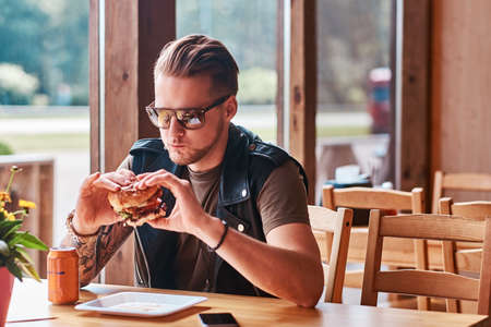Handsome hipster with a stylish haircut and beard sits at a table, decided to dine at a roadside cafe, eating a hamburger. Reklamní fotografie