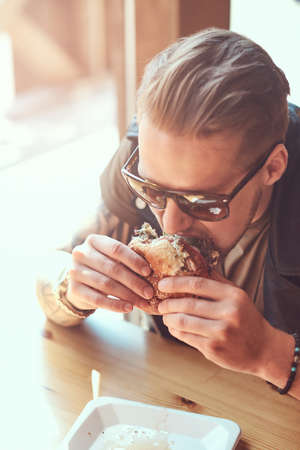 Portrait of a hungry hipster guy with a stylish haircut and beard sits at a table, decided to dine at a roadside cafe, eating a hamburger.