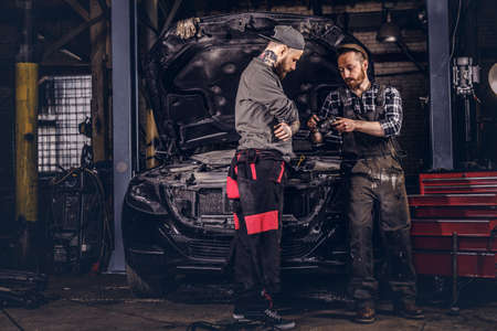 Two mechanics talking during repairs a broken car in a garage.