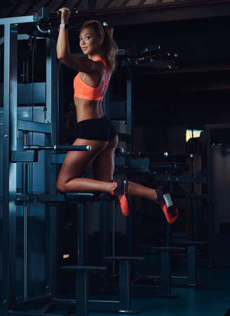 Young charming blonde woman in sportswear does pull-ups on a graviton machine in the modern fitness center. Imagens