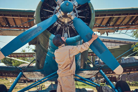 Pilot or mechanic in a full flight gear checks the propeller of his retro military aircraft before a flight.