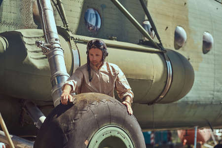 Mechanic in uniform and flying helmet wash large military helicopter.