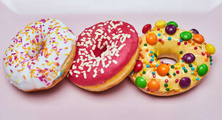 Three appetizing donuts lie on a pink ceramic plate.