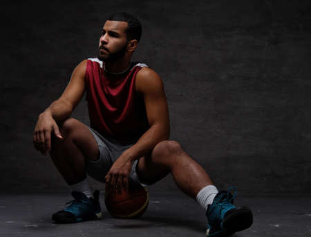 Young African-American basketball player in sportswear sitting on a ball on a dark background.