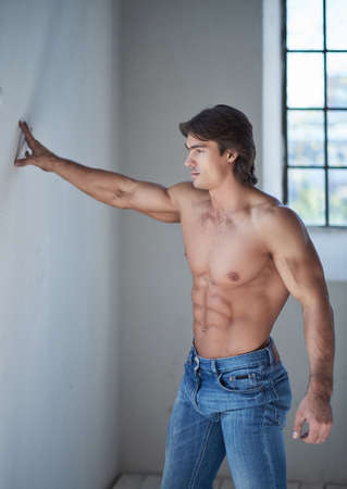 Shirtless handsome male with a perfect muscular body leaning on a wall in the studio, looking at a window. Standard-Bild