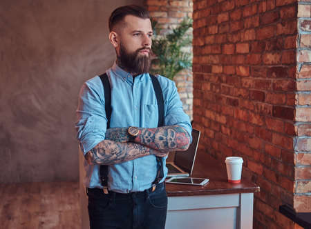 Old-fashioned tattooed hipster in a shirt and suspenders, standing near a desk with a laptop, looking out the window in an office with loft interior.