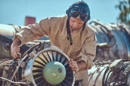 Portrait of a mechanic in uniform and flying helmet, repairing the dismantled airplane turbine.